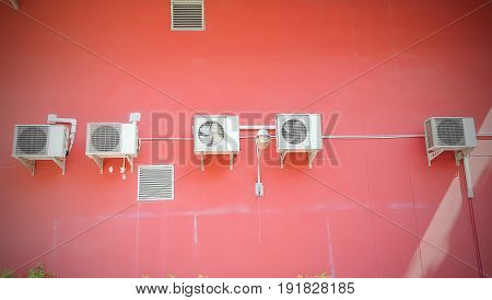 Group of compressor of air conditioner hanging on the red wall.