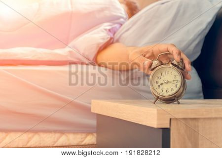 The man lying in bed is reaching out to mute the alarm clock.