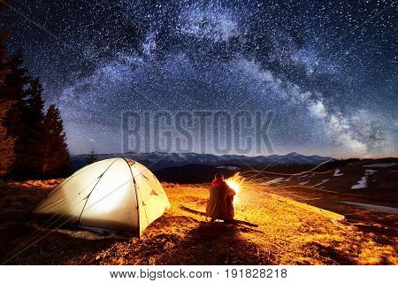 Male Hiker Enjoying In His Camp Near The Forest At Night. Man Sitting Near Campfire And Tent Under B