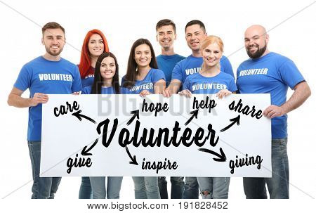 Group of people holding poster with word VOLUNTEER on white background