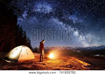 Male Hiker Have A Rest In His Camp Near The Forest At Night. Man Standing Near Campfire And Tent Und