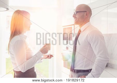 Side view of mid adult business couple talking at home