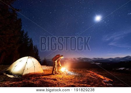 Male Tourist Have A Rest In His Camp At Night Near Campfire And Tent Under Beautiful Night Sky Full