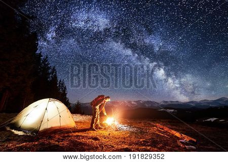 Male Tourist Enjoying In His Camp Near The Forest At Night. Man Standing Near Campfire And Tent Unde