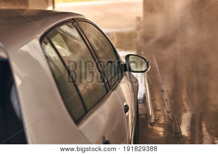 Clean silver colored automobile in car wash service interior