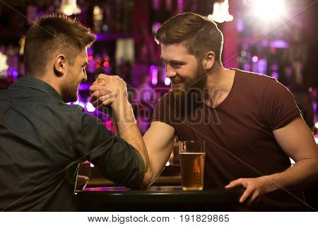 happy male friends drinking draft beer and arm wrestling at bar or pub