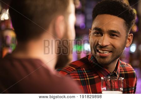 Close up of a two happy male friends drinking beer at bar or pub
