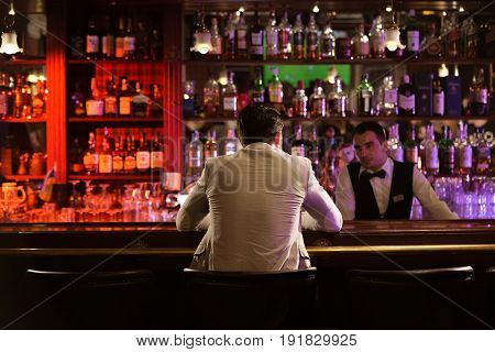 Back view of a man ordering drink to a bartender while sitting at the counter at the pub
