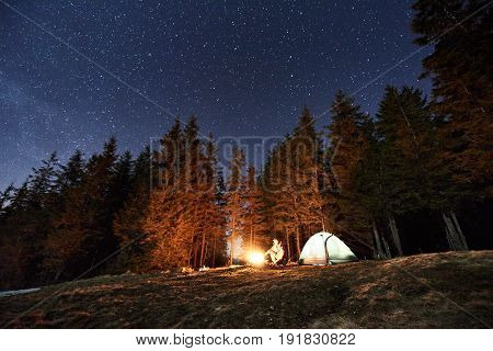 Male Tourist Have A Rest In His Camp Near The Forest At Night. Guy Is Sitting Near Campfire And Tent