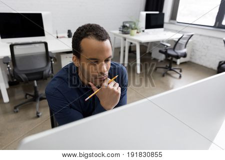 Pensive african business man looking at computer screen with hand on his chin at his workplace
