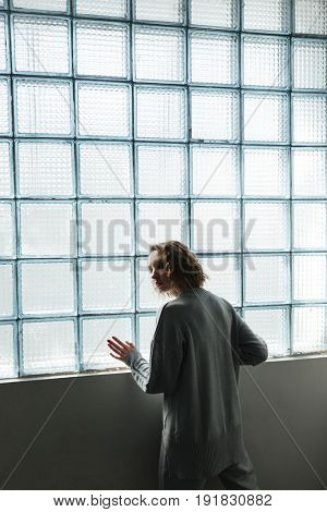 Young extraordinary girl in sportrsuit with curly hair standing near window and looking camera