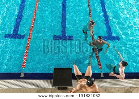 Four male swimmers chatting amongst themselves in a swimming pool