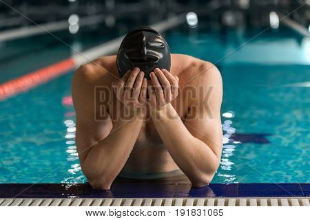 Male swimmer standing at the edge of a pool with his head in his hands