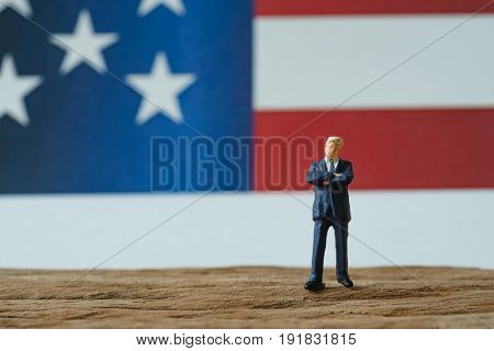 miniature people happy american businessman standing on wood floor in front of United State national flag in the background as celebrating the Independence day.
