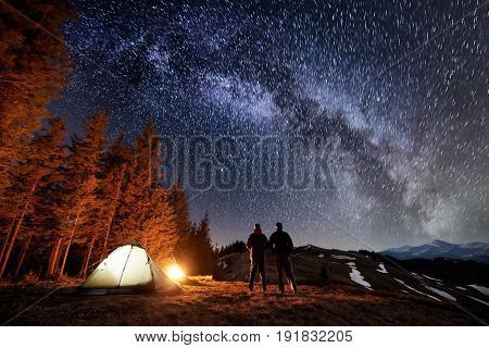 Two Male Tourists Have A Rest In The Camping Near The Forest At Night. Guys Standing Near Campfire A