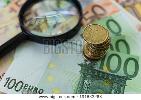 Stack of Euro coins on pile of banknotes with magnifying glass as business financial tax concept.