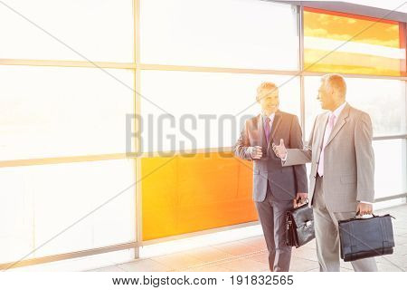 Happy businessmen talking while walking in railroad station