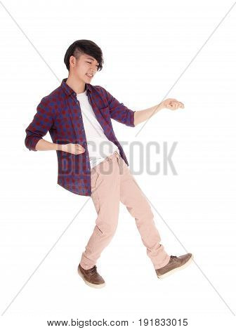 An young Asian man in a checkered shirt and sneakers dancing isolated for white background.