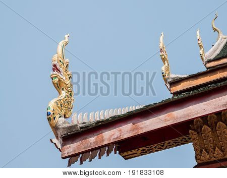Wooden dragon carving in the traditional Thai style on the eaves of the Thai temple.