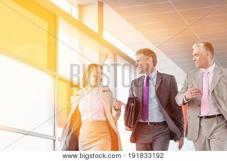 Businesspeople communicating while walking on railroad platform