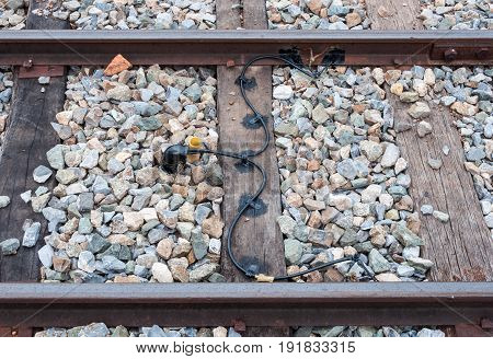 Electric wire from the black pipe for detect the train movement in the railway track.