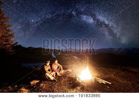 Two Male Hikers Have A Rest In The Camping At Night. Men Sitting Near Campfire And Tent Under Beauti
