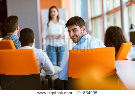 Pretty young business woman giving a presentation in conference or meeting setting. People and teamwork concept - happy creative team in office. Women in business.