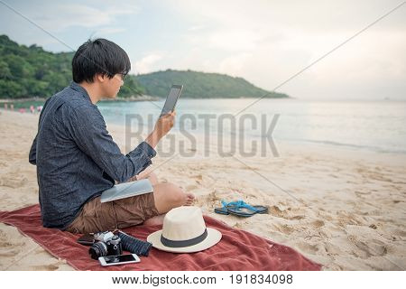 Young Asian man working using tablet on tropical beach digital nomad lifestyle or freelance occupation concepts