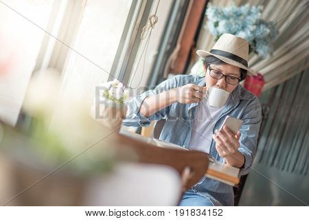Young Asian happy man text messaging on social media application by smartphone during coffee time in cafe casual lifestyle in summer holiday or vacation time concepts