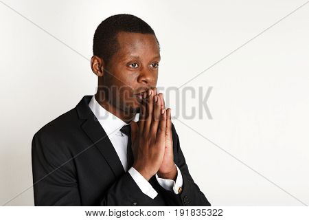 African american businessman praying copy space. Young man in suit meditating, using prayer gesture, isolated on white