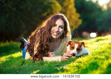 Happy young woman hugging and having fun with her Jack Russell Terrier In the blooming garden