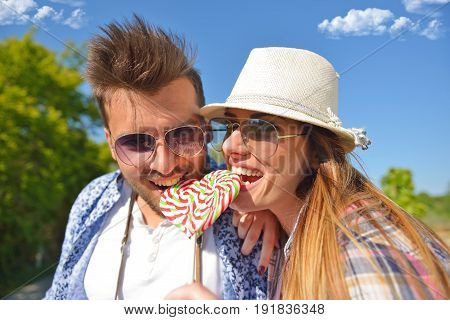 Cheerful young couple on a sunny day reading map.
