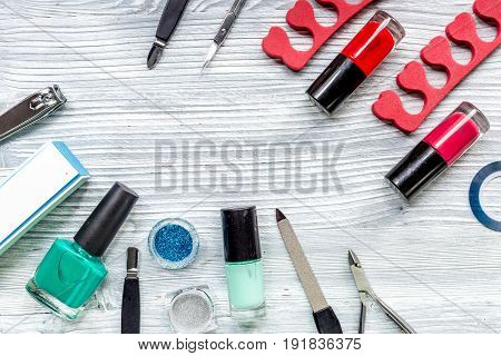 manicurist work place with manicure set and nail polish for hands care on gray wooden background top view mock up