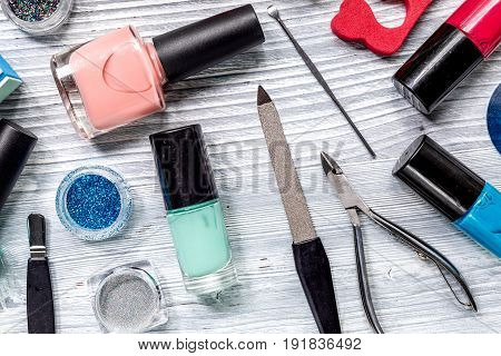 manicure and hands care set with nippers, cuticle scissors on light wooden table background top view