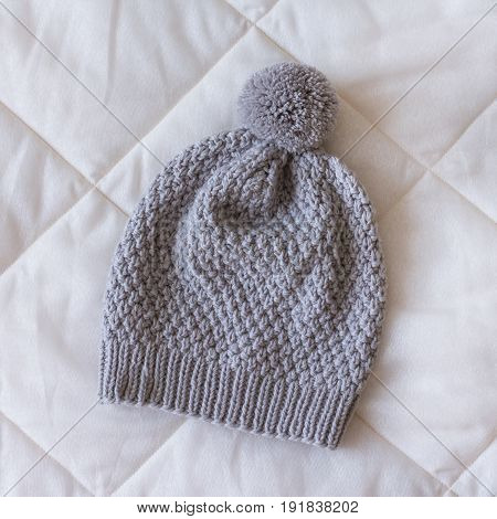 Grey Knitted Hat With A Small Pompom On A White Blanket