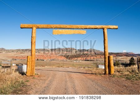 Wooden arch name plank over entrance road to a large ranch