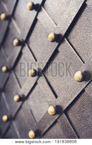 Vintage metallic pattern of medieval gate. Decorative grunge checkered iron structure background. Architectural detail vertical image, selective focus