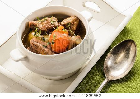 traditonal irish stew with thyme in a bowl served on a tray
