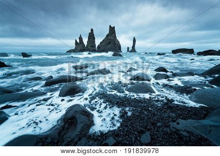 Trolls fingers. Reynisdrangar cliffs near the Vik town. Sullen landscape with the Atlantic Ocean. Tourist attraction of Iceland