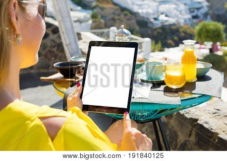 Woman using tablet computer while having breakfast vertical screen orientation