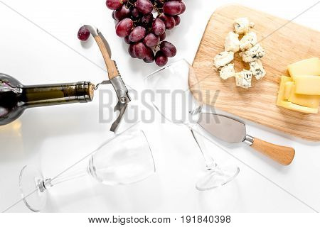 Bottle of red wine and wine glasses with cheese and grape aperitive on white background.