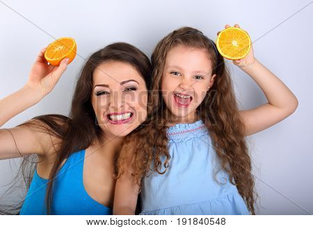 Humor Laughing Young Mother And Cute Long Hair Daughter Holding Slices Of Fresh Bright Oranges In Th