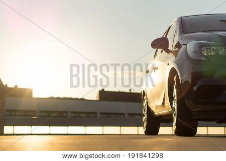 Car parked in parking lot on roof in summer time sunset or sunrise in urban city. Car background or template with copy space. Up view to modern vehicle in sun light. Building silhouettes.