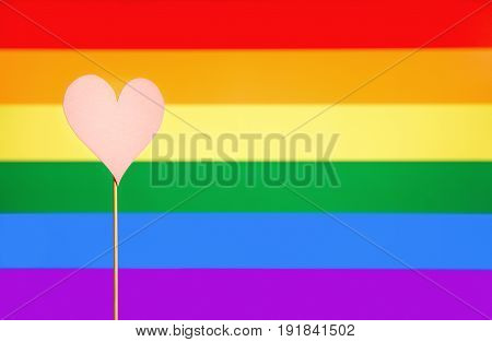 Gay pride and LGBT background. Rainbow flag design template with copy space. Heart cut from cardboard paper on wooden stick. Sexual minority, homosexuality and equal rights. Handmade love symbol.