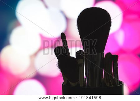 Make up brushes set silhouette with pink bokeh background. Outline of beauty products on blurred city lights. Cosmetics blenders in dark shadow at night lighting. Marketing for services or tutorials.
