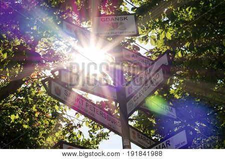 Multi direction sign in Gdansk showing the distance to the city's twin towns and sister cities. Signpost with a forest and trees in the background. Sun shining and summer feeling with lens flares.