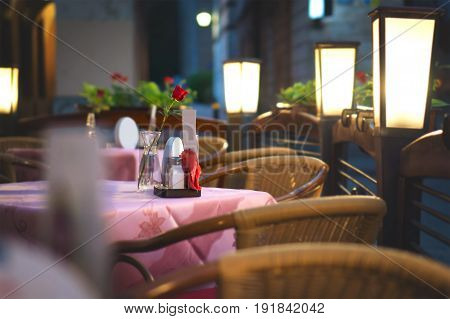 Restaurant dinner table waiting for romantic date. Ambiance lighting in empty outdoor terrace.