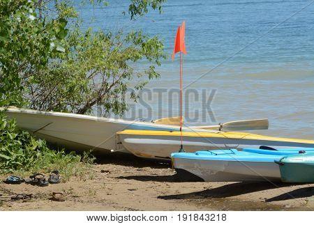 Kayaks and boats on shore of lake