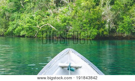 Boat approaching rocks overgrown with Palmtrees in Hidden Bay on Gam Island near Kabui and Passage. West Papuan, Raja Ampat, Indonesia.
