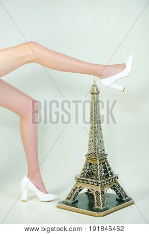 vacation. legs of woman in shoes standing near decorative eiffel tower isolated on white background travel and vacation beauty and fashion building and architecture